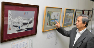 東海道五十三次の織物を紹介する内藤さん=一宮市立中央図書館で / 中日新聞